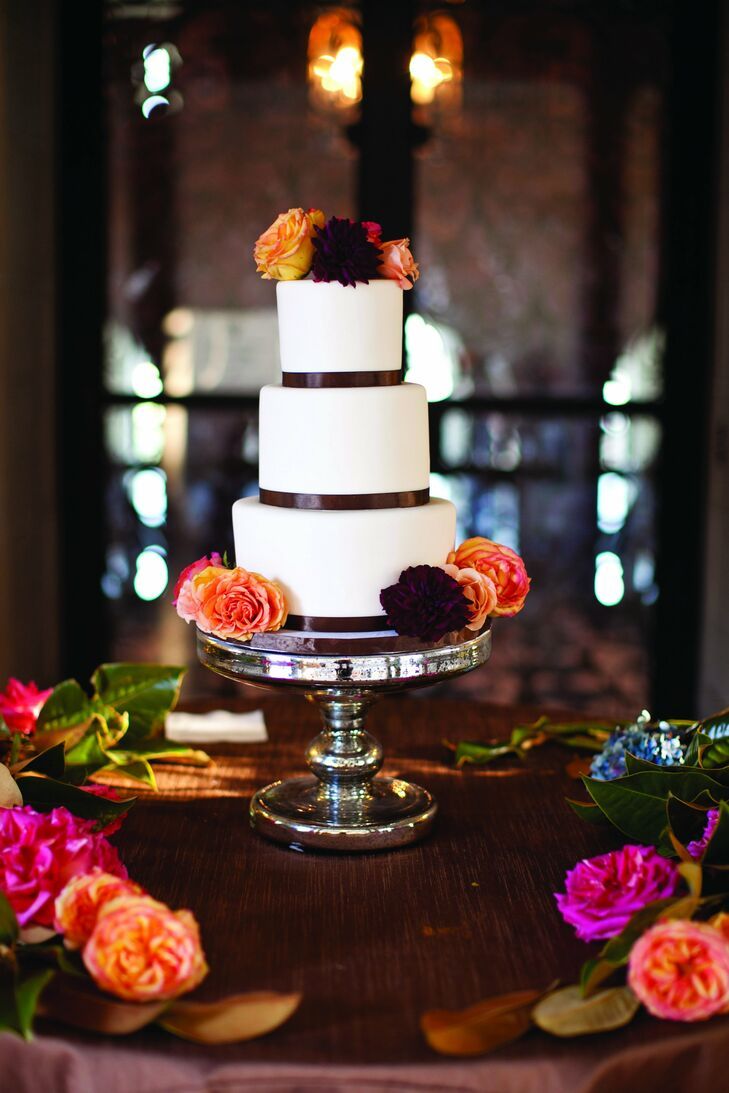The understated cake was covered in white fondant and decorated with chocolate colored ribbon and live blooms.