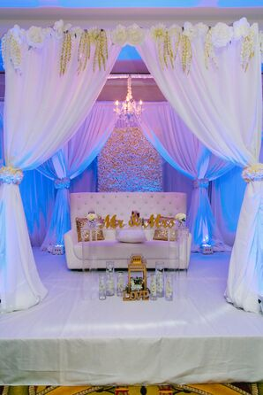 Romantic, Elevated Sweetheart Table Area with Draping and Uplighting