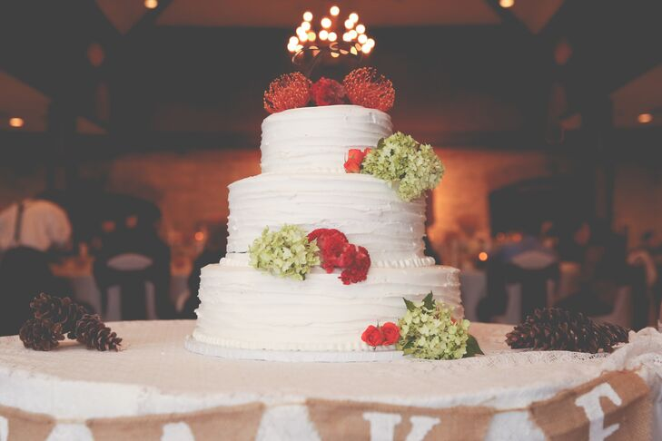 Lauren and Josh enjoyed a three-tier white buttercream wedding cake topped with pincushion protests and green hydrangeas to match the fall wedding.