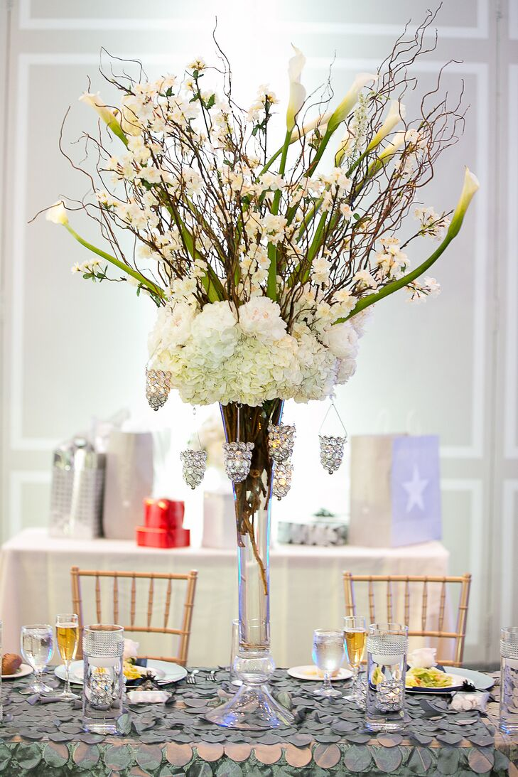 Tall, white flower centerpieces at the reception included hydrangeas, calla lilies, roses and lisianthuses in addition to branches. They were arranged in glass trumpet vases . The tablecloths at the reception were silver with rosettes.