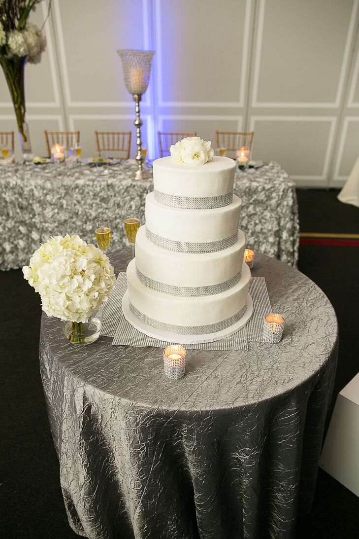 """Aaron's uncle made the four tier wedding cake, which was decorated with silver ribbon and topped with white lisianthuses. The cake was flavored """"blue velvet"""" to match with the color scheme of the wedding."""