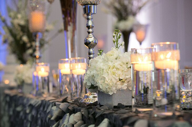 Tables at the reception were decorated with floating candles in glass vases and silver candlesticks as well as small arrangements of white hydrangeas.