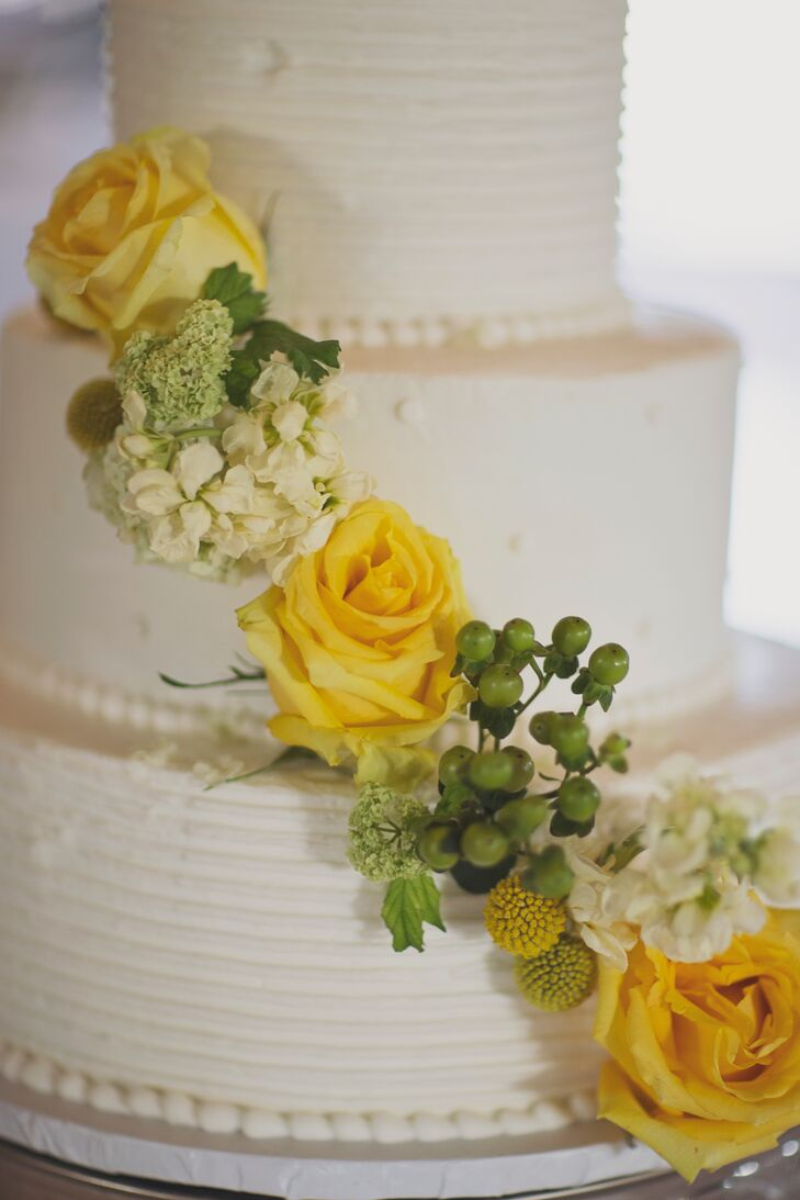 Lauren and Bryan enjoyed a three-tier buttercream cake decorated with yellow roses and green hypericum berries.