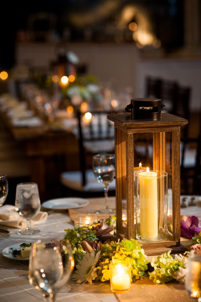 Black lanterns with candles were wreathed with hydrangeas, viburnum, gerber daisies and other flowers to create the centerpieces at the reception.