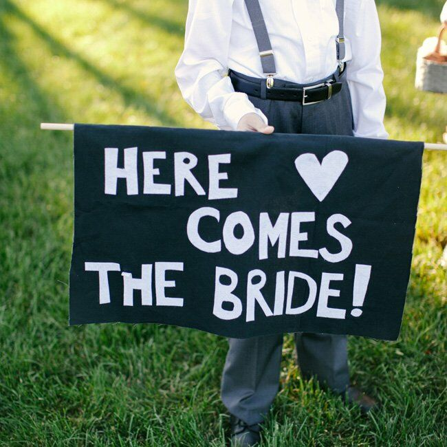"""Logan, a boy Tiffany used to nanny, walked down the aisle with a sign reading """"Here comes the bride!"""""""