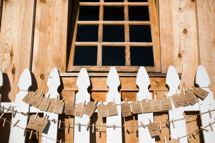 Kraft-paper escort tags tangled from wire, strung across a white picket fence that leaned against the barn at Amador Cellars in Plymouth, California. This display followed the day's rustic-chic theme and country style.