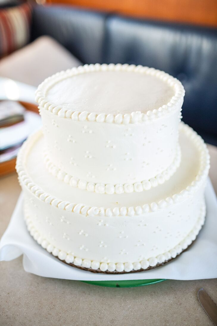The couple served a two-tier, white iced wedding cake with a simple, piped detailing.