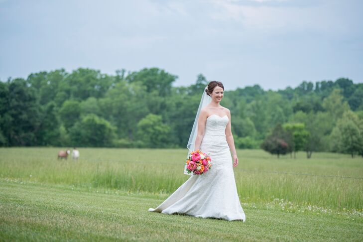 Andrea wore an intricate lace A-line dress with a strapless sweetheart neckline and chapel-length train. She also wore a single-layer tulle fingertip-length length veil.