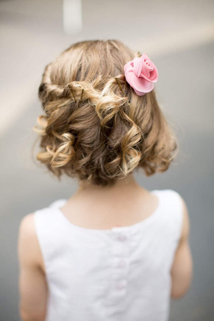 A pink rose decorated the flower girl's soft curled hairstyle.