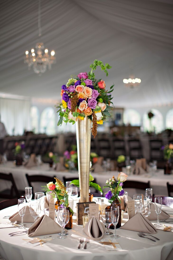The tented reception featured tall gold pilsner vases filled with blush, coral and lavender roses, sunflowers and greens. These added height to the space, which was illuminated by crystal chandeliers.