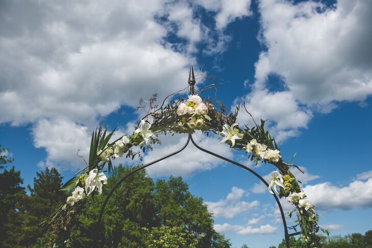The wedding arch was decorated with white hydrangeas, white roses and white lilies for the spring reception.