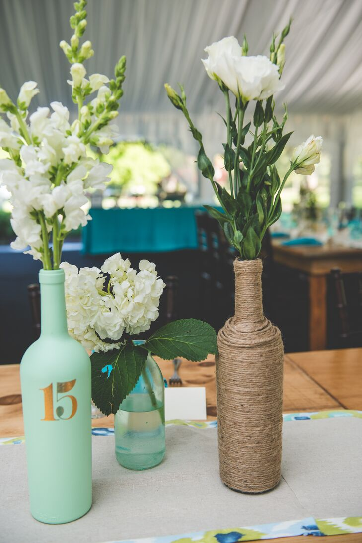 Centerpieces consisted of bottles painted turquoise and wrapped in twine, which were filled with white delphiniums, white roses and white hydrangeas. Some had table numbers stenciled onto them.