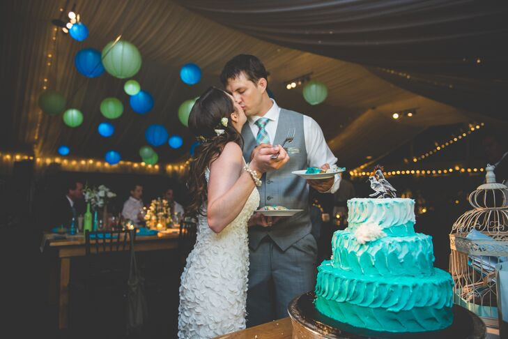 The tented reception was illuminated with string lights and green and blue lanterns. The cake was turquoise ombre with a glass bird topper.