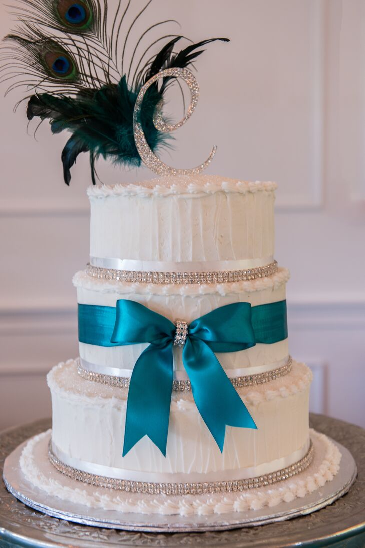 A blue ribbon tied in a bow, crystal accents and a peacock feather (of course!) added some glamor to the couple's white wedding cake.