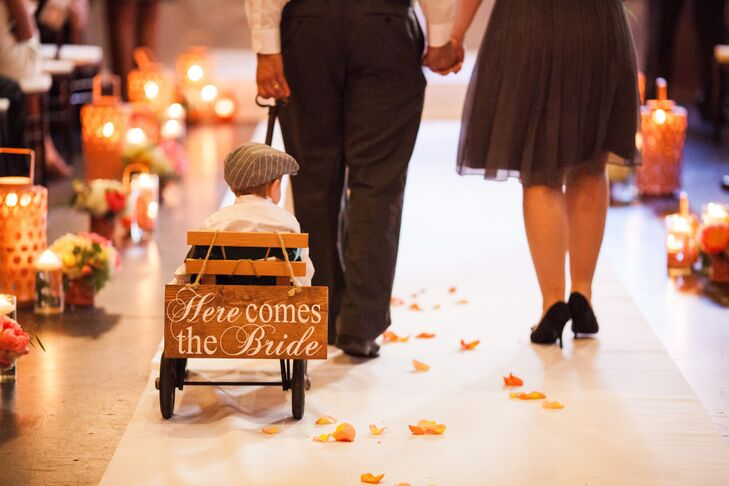 """Since the ring bearer was too young to walk down the aisle, his parents pulled him in a little wagon behind the flower girl. His little cart was decorated with a wooden sign that said """"Here Comes the Bride"""" on the back."""