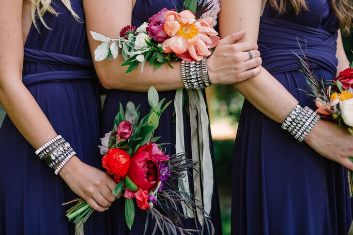 The bridesmaids wore infinity convertible dresses in a rich blue hue, which allowed them to customize their styles. They also selected their jewelry—matching crystal bangles—from Shelly Brown, and carried hand-tied bouquets in shades of rich red, pink and green.