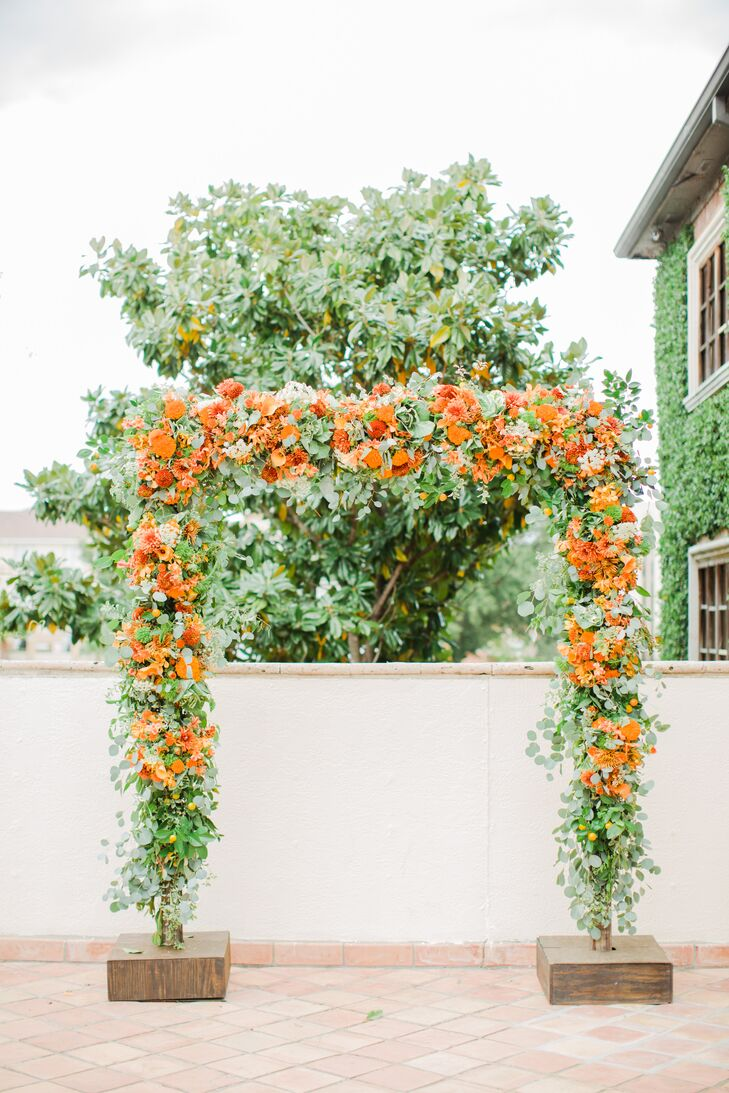 SCF Events covered this wooden wedding arch in vibrant orange flowers and greenery for a wow-worthy display. It had flame callas, pincushion proteas, orchids, dahlias, chrysanthemums and little orange fruits with eucalyptus and greens.