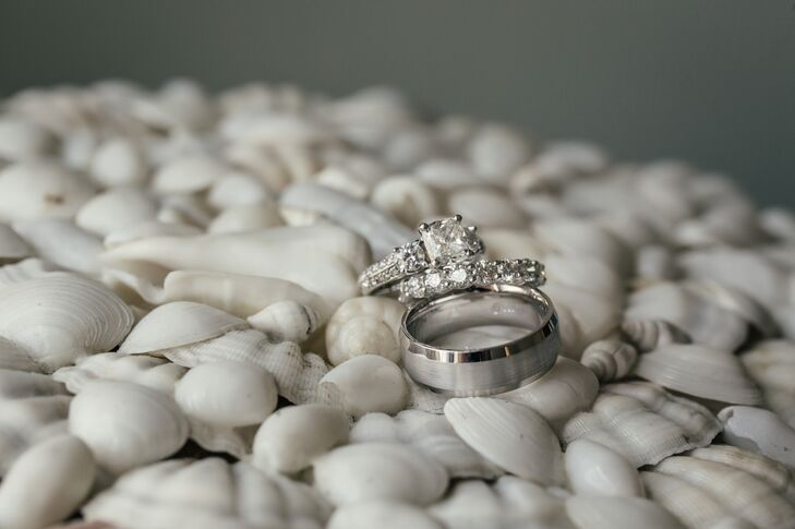 Kyle proposed to Kylie on his college campus with a classic princess-cut diamond ring surrounded by two round diamonds and diamond baguettes. For their ceremony, she picked out a matching wedding ring surrounded by round diamond baguettes. Kyle went with something just as timeless and chose an all-silver band.