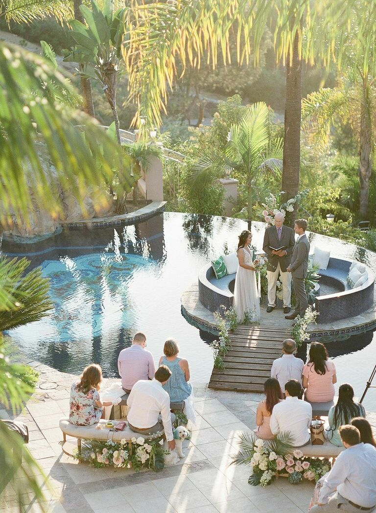 Couple exchanging vows beside swimming pool