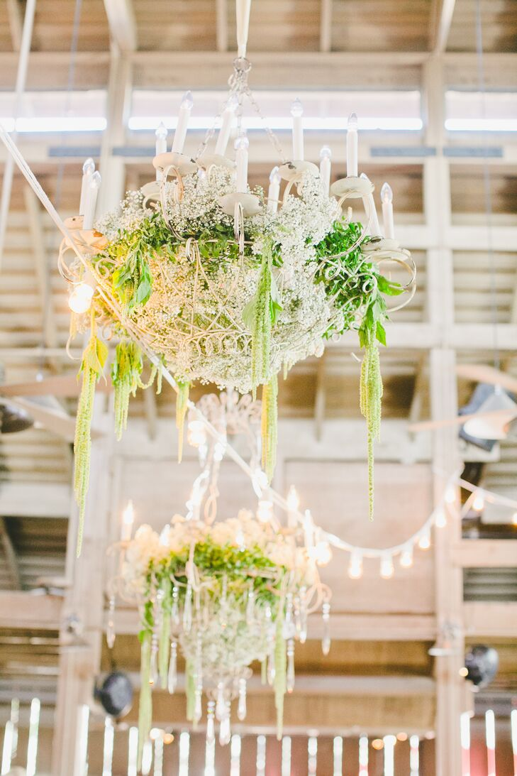 White elegant chandeliers dangled from the ceiling inside the barn, overflowing with greenery that hung close to string lights illuminating the space.