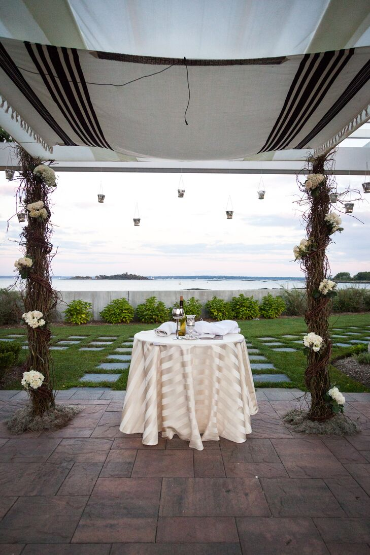Emma and Michael's chuppah took on an entirely different look from the rest of their decor. Natural vines covered every post with pops of white hydrangeas. Silver votives were even hung along the sides.