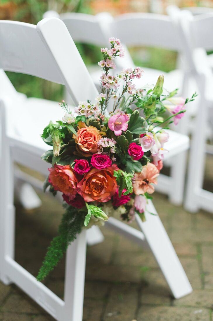 Orange and pink blooms filled the bouquets that marked the aisles at the ceremony.
