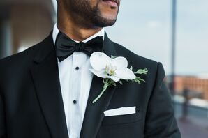 White Orchid Boutonniere Against Black Tuxedo