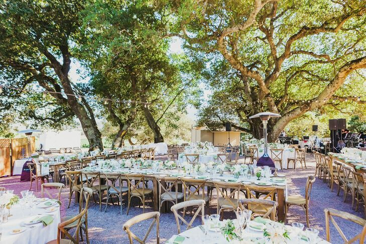 At the outdoor reception, the natural beauty of Sonoma Valley wine country was on full display. Round and longer farm tables were arranged under market lights. In keeping with the naturalistic green and cloud white palette, verdant bay leaf garlands were laid alongside ivory lace runners on the farm tables.