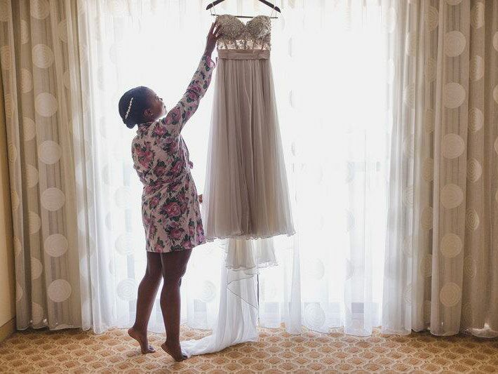 Bride with her wedding dress hanging up