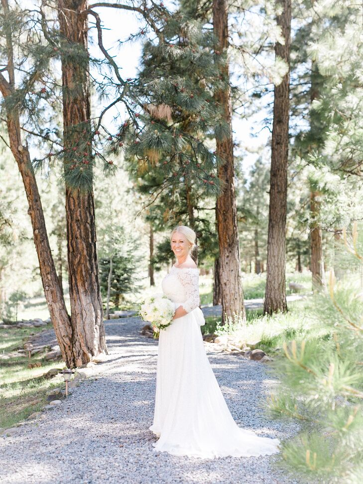"""""""Once again, I have always wanted a timeless look and feel for my wedding dress,"""" says Kassi, who chose a long-sleeved gown by Amy Kuschel. """"The dress has a lace top with a silk and chiffon overlay for the bottom. It had an empire waistline and the option for a topper. I knew that for the ceremony I wanted a modest look, so the option for the lace topper was perfect."""""""
