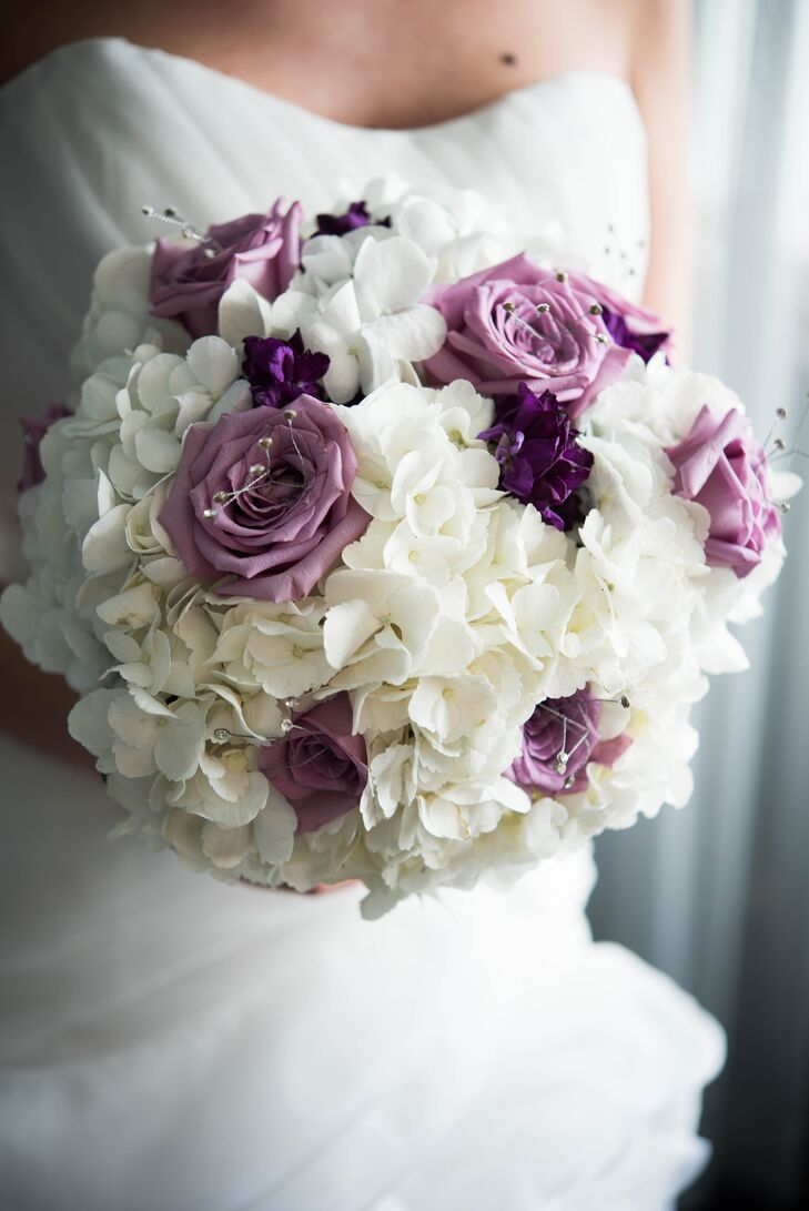 White and lavender roses were mixed with hydrangeas to create the bride's glam bouquet. For a similar aesthetic, purple calla lilies were used in each of the men's boutonnieres.