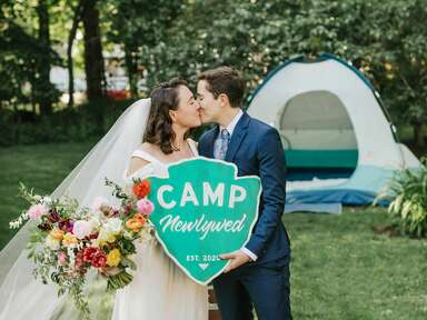 Couple kissing while holding camping-themed sign