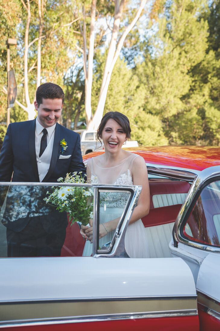 Beth and Jonathan stood near a classic red and white car that went along with their retro style. Jonathan wore a navy suit and matching tie on the day of the wedding, along with an ivory vest that matched Beth's wedding dress.