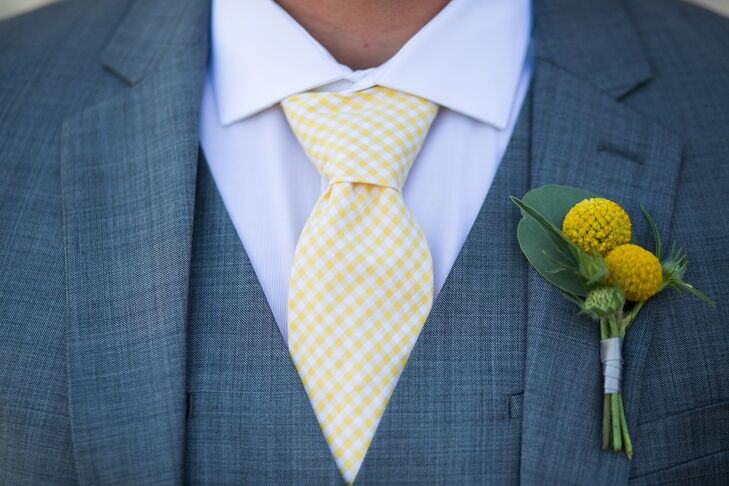 Drake pinned a yellow craspedia boutonniere to the lapel of his three-piece suit jacket, which he paired with a light yellow and white gingham tie. His wedding day look fit the yellow and gray color scheme at large.