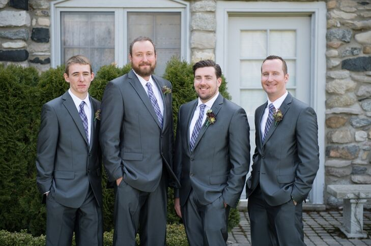 "Each of the groomsmen wore gray suits paired with purple and gray plaid ties. ""We wanted a classy, elegant look that still matched with the rustic feel of our venue,"" Cortney explains."