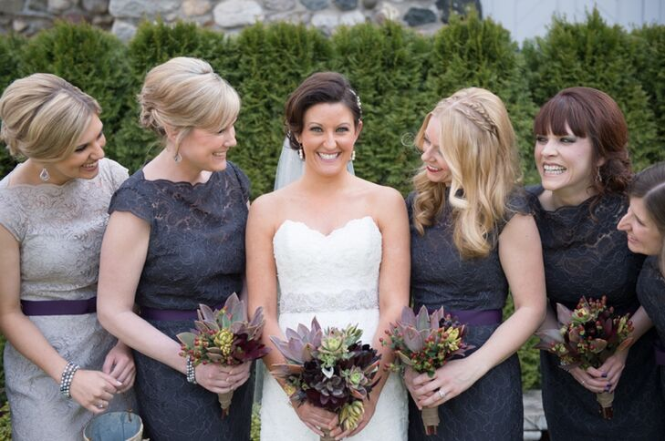 The bridesmaids wore charcoal lace dresses with eggplant-colored belts.