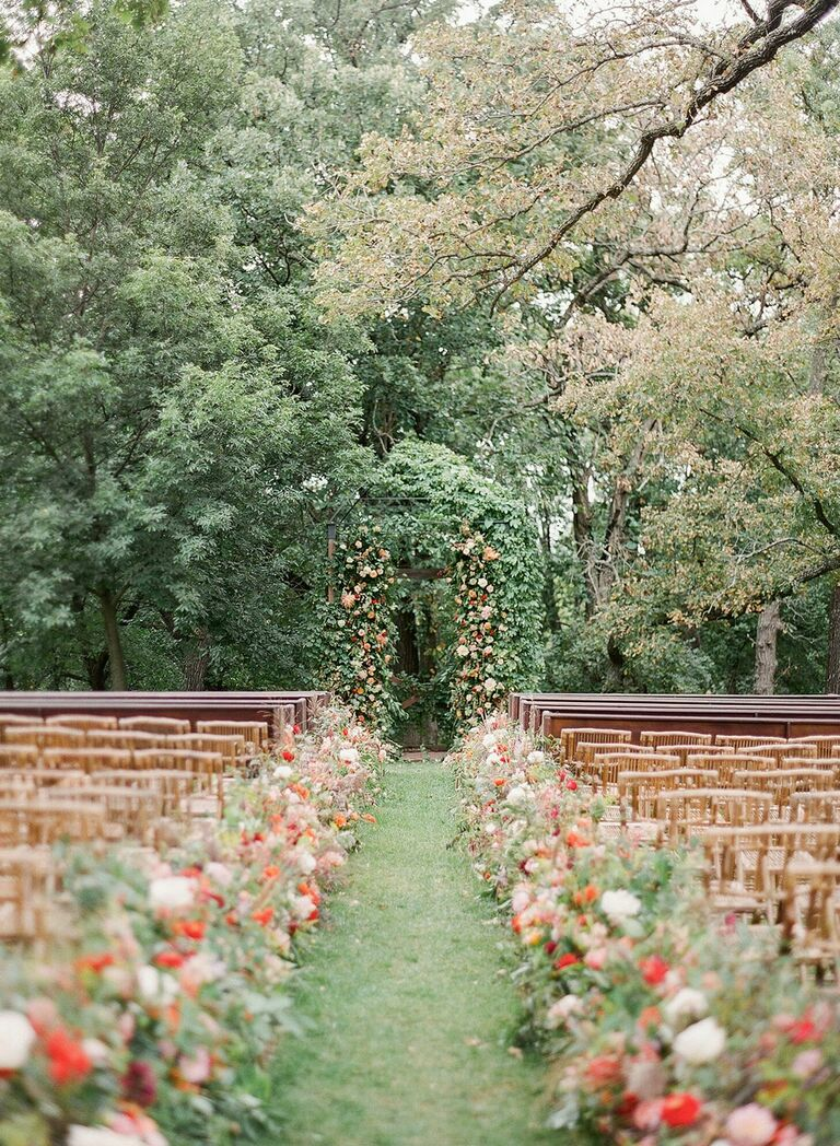 Outdoor wedding ceremony with floral-lined aisle and floral arch