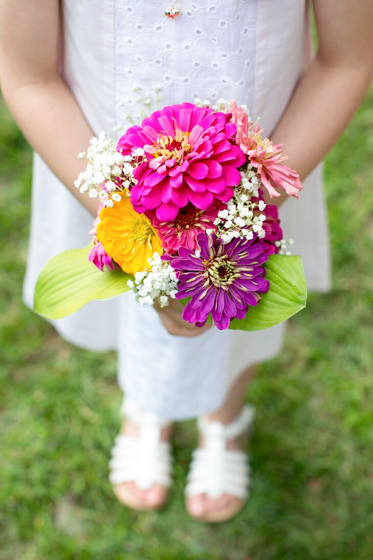 The flower girl carried a small bouquet of fuchsia zinnias accented by small sprigs of Baby's Breath.
