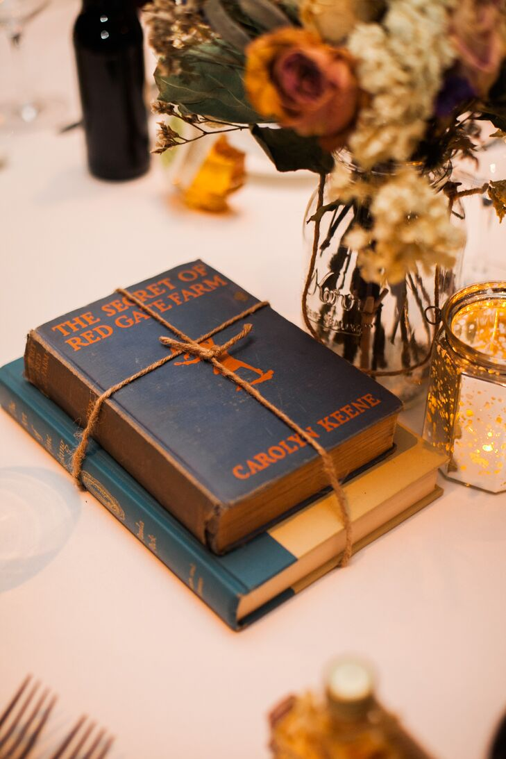 The couple used vintage books wrapped in twine as centerpieces during their vintage-inspired reception.