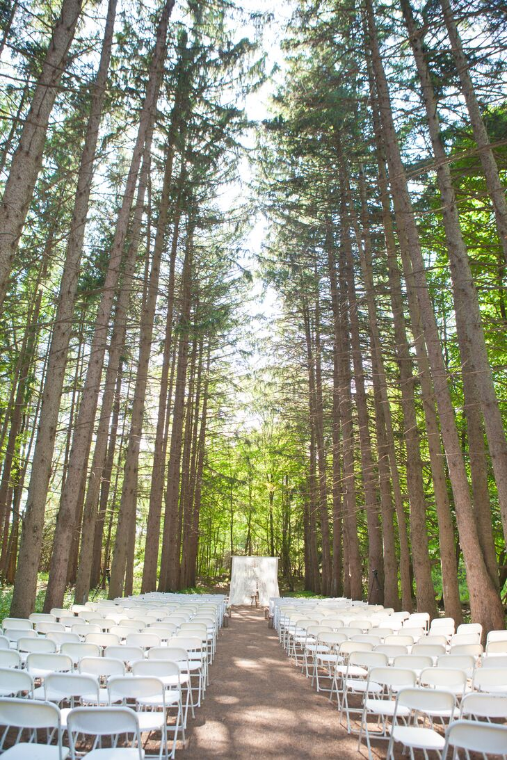 """The ceremony took place in an outdoor setting at Stony Creek Metropark in Shelby Charter Township, MI. """"The tall white pine trees that build a cathedral in the middle of the woods with shafts of light beaming through the trees was perfect for our ceremony,"""" Adrienne shared."""