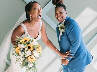 Couple laughing while posing with sunflower wedding arrangements