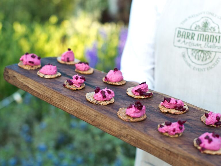 Pureed beet appetizers on a rustic wooden tray.