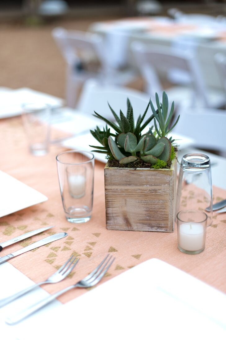Phuong of Mibellarosa Designs suggested adding goemetric paper origami and table runners to tie Minh and Miguel's geometric peach and neutral aesthetic together. Minh painted gold triangles on peach crepe paper for the table runners, and potted succulents on wooden slabs or boxes completed the clean, rustic look.