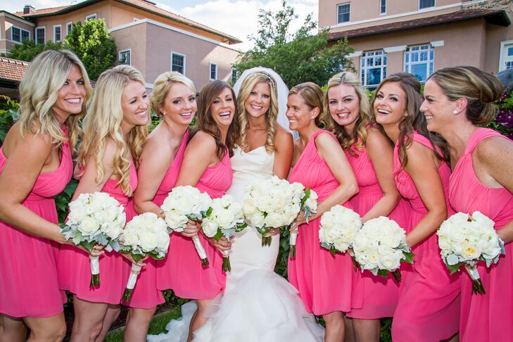 The bridesmaids wore bright pink cocktail-length dresses with one shoulder strap.