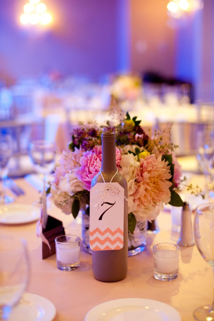 Caitlin and Benjy spray painted win bottles silver and hung pink chevron tags around them with the table numbers.