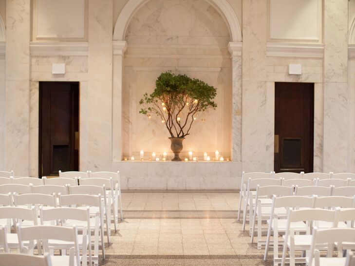 """The couple's ceremony was understated yet chic with a stone urn filled with manzanita branches that were decorated with hanging votive candles. """"We tried to keep everything simple, natural and elegant to go with the space,"""" Sydney says."""