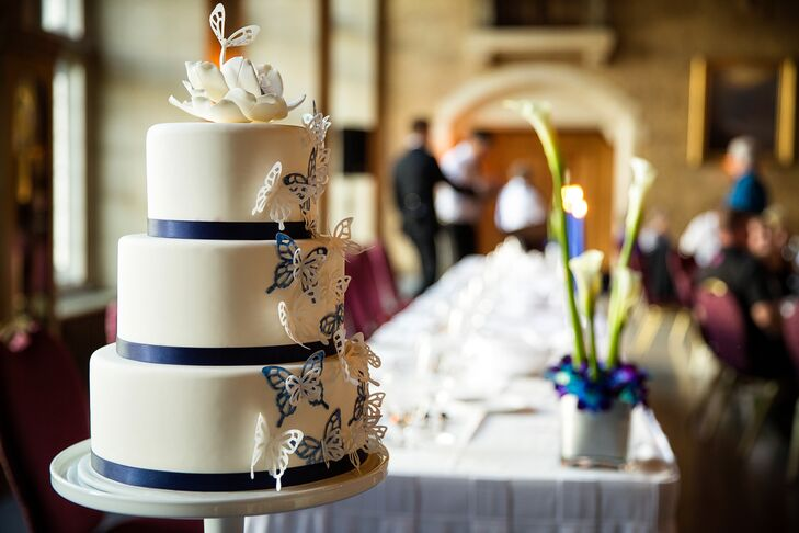 """The three tier white cake had white and blue butterflies """"flying"""" up the side of the cake."""