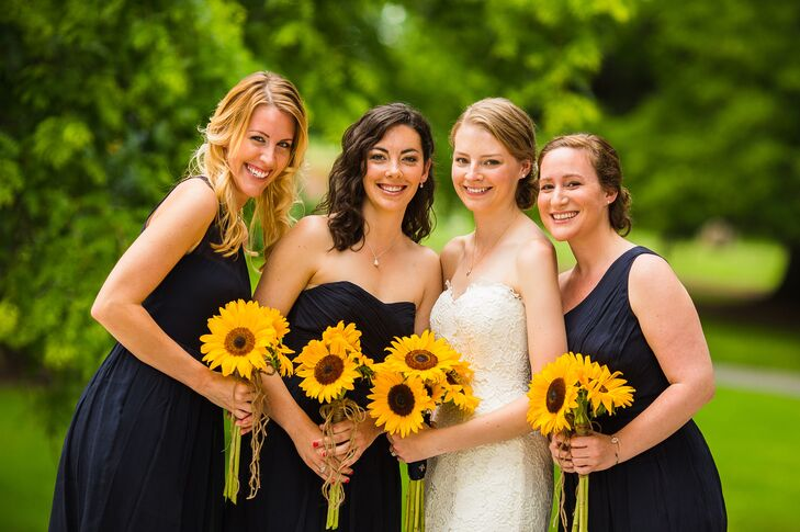 Reagan's bridesmaids wore navy dresses from J.Crew in various styles and carried sunflower bouquets.