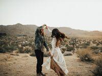 Bohemian bride and groom dancing in desert on wedding day