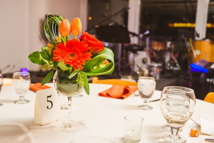 The reception tables were topped with wineglasses filled with orange roses, tulips, gerbera daisies, green seeded eucalyptus, hypericum berries and leaves. Laura and Amory chose the bold orange and green color palette to accent the exposed brick and rustic feel of the reception space.